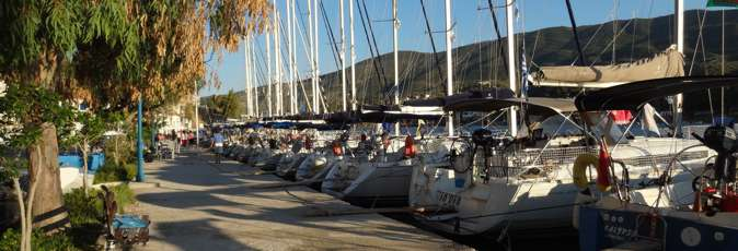 Greek Sails yachts sit in the sun on the Poros quayside awaiting their next flotilla holiday and bareboat yacht charter sailing holiday crews