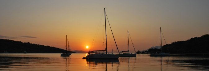 The sun rises over the harbour at Paleo Epidauros silhouetting moored sailing yachts