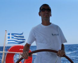 A Greek Sails skipper helms while the crew relax, enjoying their sailing holiday