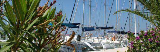 Greek Sails flotilla holidays & bareboat charter fleet at their sunny base in Poros quayside awaiting their next flotilla and bareboat sailing holiday crews