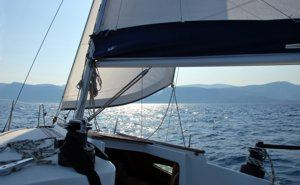 The afternoon sun glistens behind the genoa of a Greek Sails Sun Odyssey 29.2 yacht