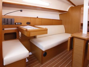 The navigation table & port-side sofa aboard the Jeanneau Sun Odyssey 33i sailing yacht