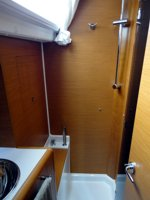 The main cabin shower of the Jeanneau Sun Odyssey 409 sailing yacht, with toilet behind you and separated from the shower by a folding screen