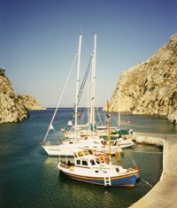 Bareboat charter yachts nestle in an inlet on the Clyclades islands, Greece