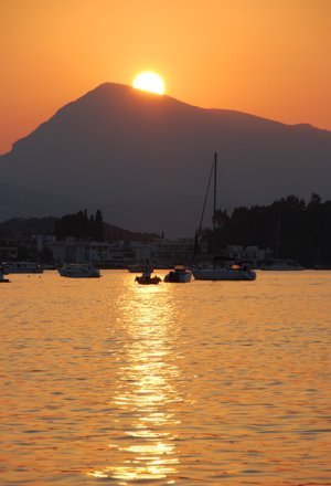 The sun sets behind the knees of the Lady of Poros, Peloponnese, Greece